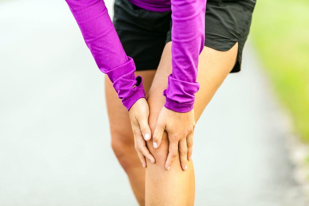 Läuferin hält sich das Knie vor Schmerzen